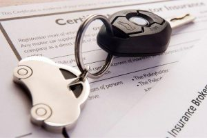 car keys sitting on top of insurance papers